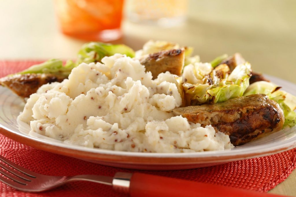 This main course dish combines healthier chicken sausage with cabbage and fluffy mashed potatoes that get a flavor boost from whole grain mustard.
